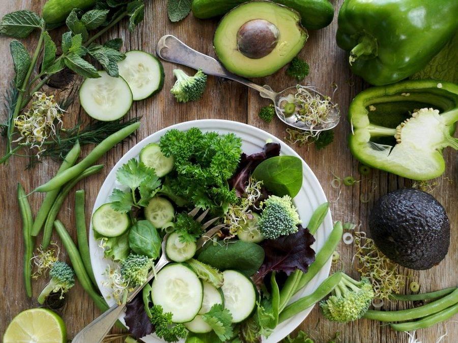 gröna grönsaker och blad med klorofyll. Grönsaker ligger upphackade i en vit skål som står på ett brunt träbord. Runtomkring ligger grönsaker uppskurna samt en silversked med groddar i. Avokado, paprika, broccoli, bönor, sockerärtor, alfalfagroddar, gukra, lima, mynta, spenat, groddar, persilja, salladsblad, zucchini, salladslök, och koriander.
