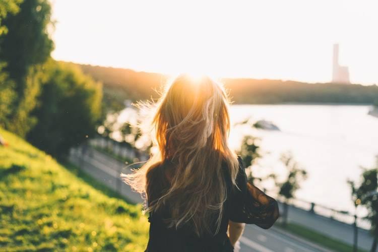 kvinna fotad med ryggen mot kameran med blont utsläpps hår nerpå ryggen. Hon tittar ut mot vatten i en stad, med gräsmatta och träf runtomkring. Solen lyser i hennes ansikten och längre bort syns en hög byggnad. Träning innan frukost