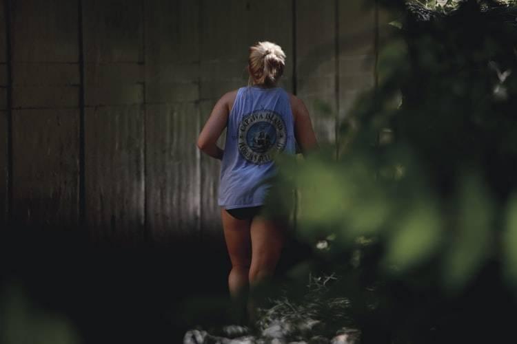 Kvinna med blont hår uppsatt i tofs, blått linne och short är ute på springrunda. Fotot är taget bakifrån på kvinnan med växtlighet bredvid. På linnet har hon ett stort tryck över ryggen. Fysisk aktivitet under klimakteriet