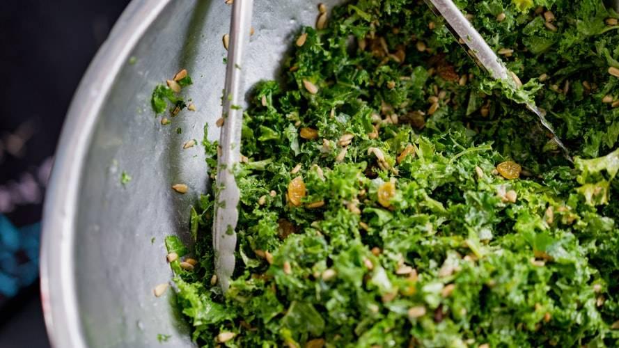Sallad på gröna blad ligger upphackade smått i en skål av rostfritt stål med en tång av stål i. I salladen ligger små gula russin samt frön.