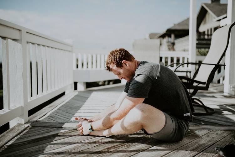 Man strechar på altan med vita räcken framför sig. Det ser ut att var morgon. Killen har svarta shorts och mörkgrå tshirt på sig och kortklippt rött hår. Han sitter framhukad över benen med benen vikta in mot varandra. Bredvid manenn står ett par svarta stolar. Morgonstrech