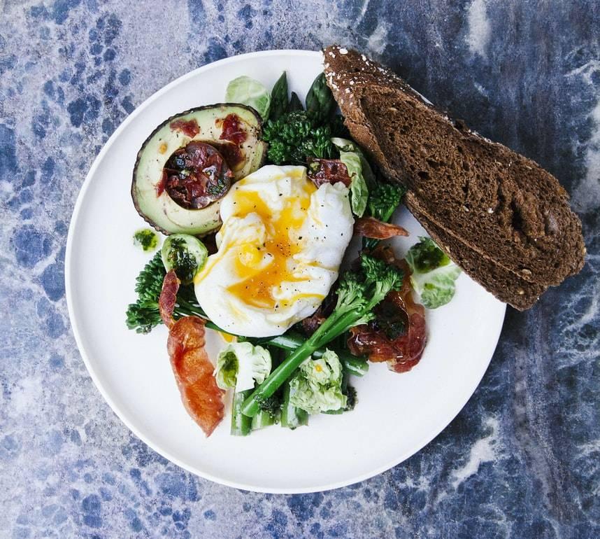 Vit tallrik med grönsaker, sallad, halv avokado, ägg och mörkt bröd. Tallriken står på ett blått bord. Ägget ligger ovanpå grönsakerna och brödet skuret och ligger på sidan av tallriken.
