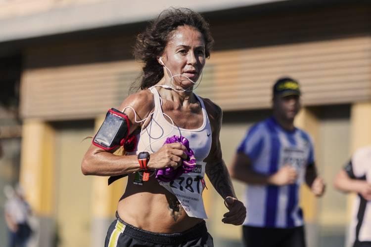 Kvinna springer maraton eller annant långdistanslopp. Hon har på sig ett vitt linne med lapp med siffror på, svarta shorts och en telegon på armen i en armväska. På magen har hon en tatuering och en klocka på handleden. Hon har svart hår uppsatt. I bakgrunden syns en man med vitblå randig tröja och keps.
