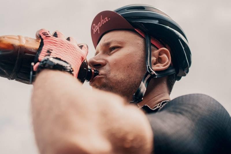 Man dricker ur en plastflaska när han cyklar under träning eller tävling. Bilden är tagen på den övre delen av mannen med huvud och delar av överkroppen. På huvudet har mannen en keps och ovanpå en hjälm. På händerna han röda cykelhandskar.