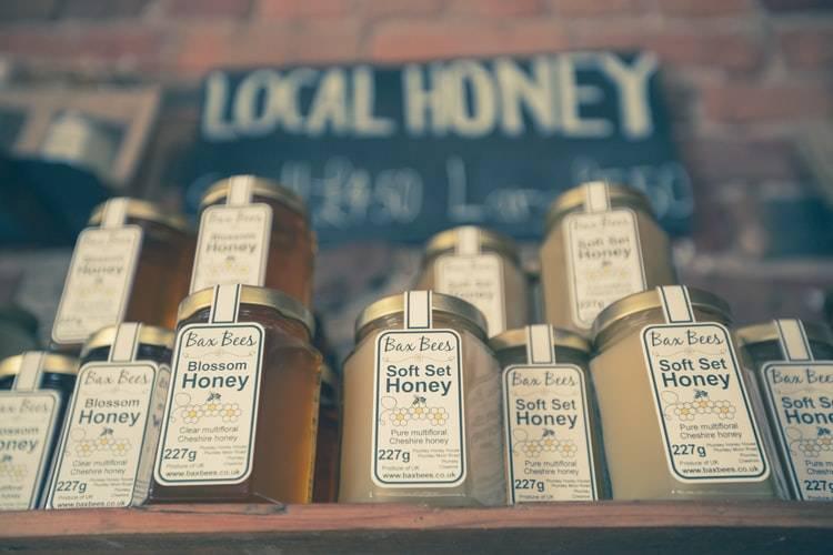 """Lokaltprducerade honungsburkar står uppradade och på varandra på en hylla i butik. Bilden är tagen snett nedifrån. Burkarna står på en trähylla och ovanför hänger en svart skylt där det står """"lokalproducerad honung"""" som hänger på en vägg av tegelstenar. Burkarna är sexkantiga och har en etikett på sig med text samt enkla färger."""