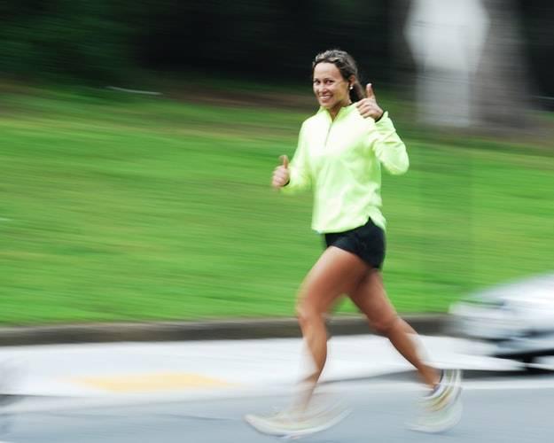 Kvinna springer på asfalt och ler mot kamera med tummen upp. Hon har på sig ett par svarta shorts och en limegrön löparjacka. Kvinnan har håret uppsatt i tofs och ser glad ut. Bilden utöver henne är suddig med en bil i bakgrunden och gräsmatta. Träna under den hormonella cykeln