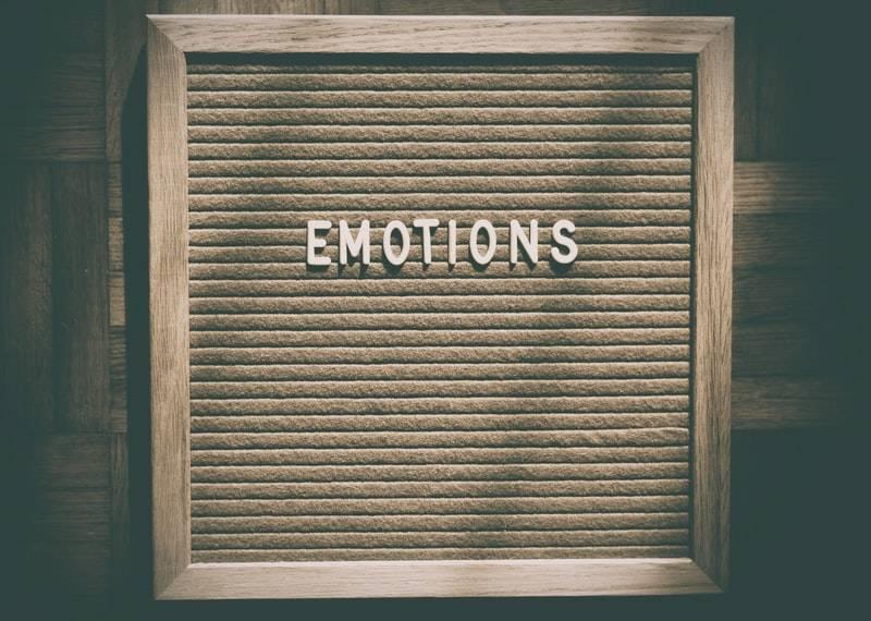 """Trätavla med enbart ett ord """"emotions"""" eller känslor på svenska. Vilket står med stora vita bokstäver. högkänslig med många känslor"""