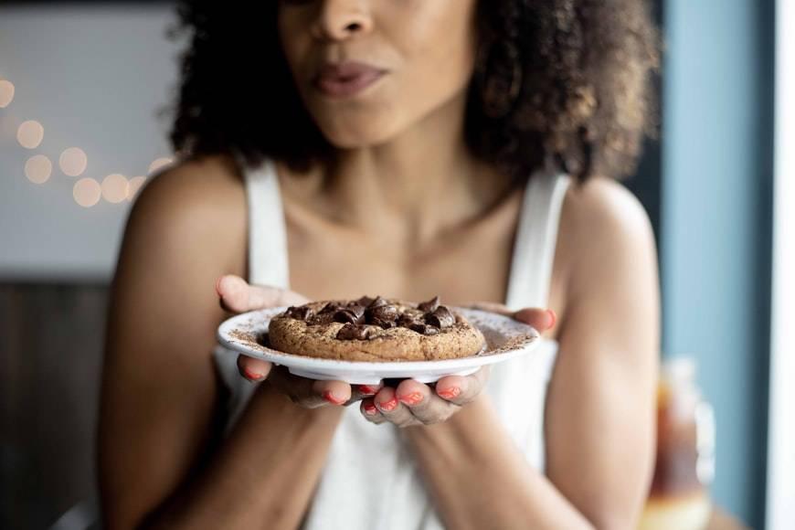 Kvinna håller fram en vit tallrik med en stor kaka på. Kakan har chokladchips på toppen. Kvinnan har brunt lockigt hår till axlarna, målade naglar och ett vitt linne.
