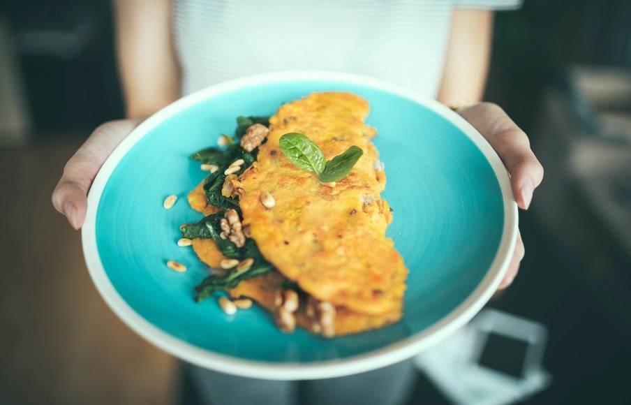Kvinna håller en blå tallrik med vita kanter. På tallriken ligger en omelett ihopvikt med gröna blad och valnötter mellan. Ovanpå ligger några blad basilika. Bilden är tagen på kvinnans händer och en del av överkroppen, inte huvudet.