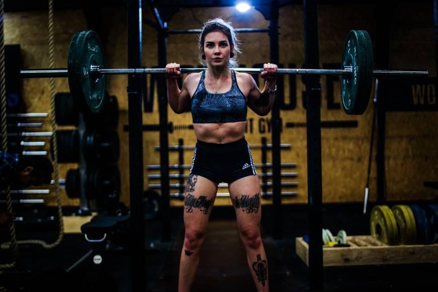 Kvinna tränar styrketräning på gym. Hon har en stång med tunga vikter på axlarna och tittar rakt fram. Hon håller händerna runt stången och står bredbend. Kvinnan har en blå sportbh på sig och ett par svarta hotpants. På benen har hon flera tatueringar. I bakgrunden syns massa vinter och stänger.