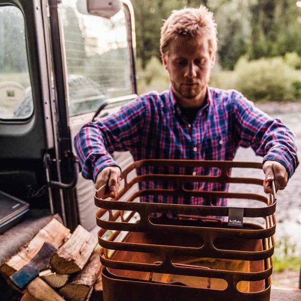 Man lyfter av Höfats Cube Eldkorg & Kolgrill från bil