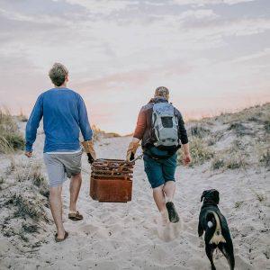 2 kompisar bär Höfats Cube Eldkorg & Kolgrill till stranden