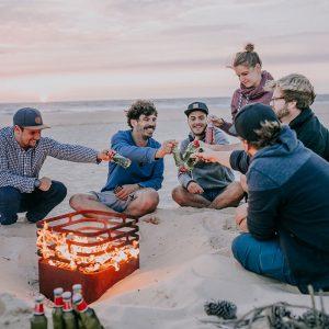 Kompisgäng sitter runt Höfats Cube Eldkorg & Kolgrill rost på stranden