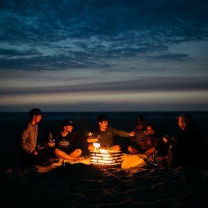 Kompisgäng sitter runt Höfats Cube Eldkorg & Kolgrill rost på stranden på kvällen