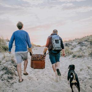 2 kompisar bär Höfats Cube Eldkorg & Kolgrill rost till stranden