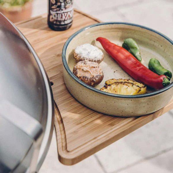 Skål med grillad mat ovanpå Höfats Cone Avlastningsbord
