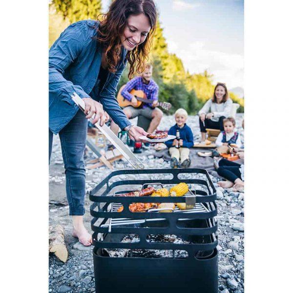 Kvinna plockar upp grillad mat med tång från Höfats Cube Eldkorg & Kolgrill