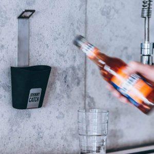 Flaska på väg att öppna kapsyl med hjälp av Höfats Johnny Catch Cup Kapsylöppnare