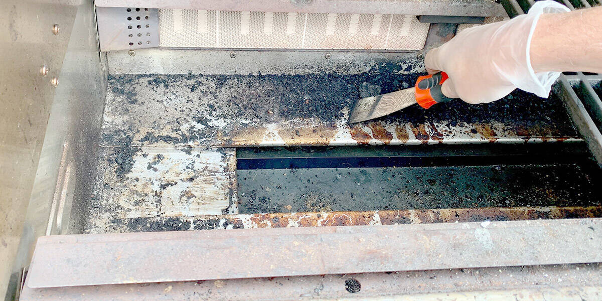 Botten av gasolgrill rengörs med hjälp av skrapa