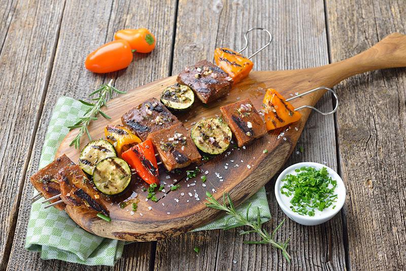 Grillad tofu på grillspett med grönsaker på skärbräda med tzatziki i en liten skål bredvid