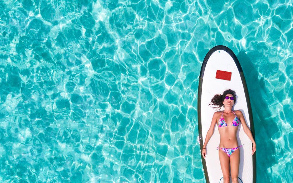 Woman in bikini lying on paddleboard in water. Above her head is a red keyboard.