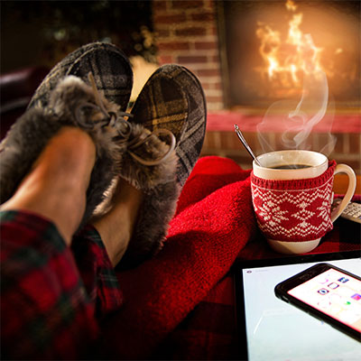 Photo of a person's feet up with slippers on by a roaring fire with a hot drink