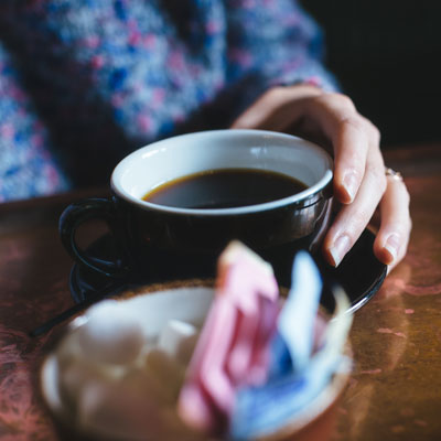 Photo of someone's hand with a cup of coffee