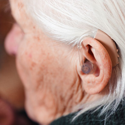 Photo of an older person wearing a hearing aid