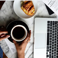Photo of someone holding a cup of coffee sitting next to a laptop and a plate with a pastry on it