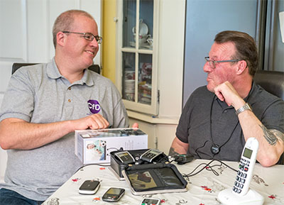 Photo of equipment officer Piers demonstrating some phone equipment to a client at home