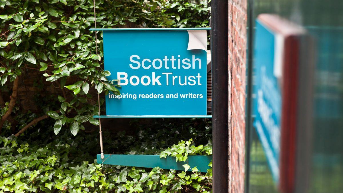 Scottish Book Trust blue sign, surrounded by a lush hedge