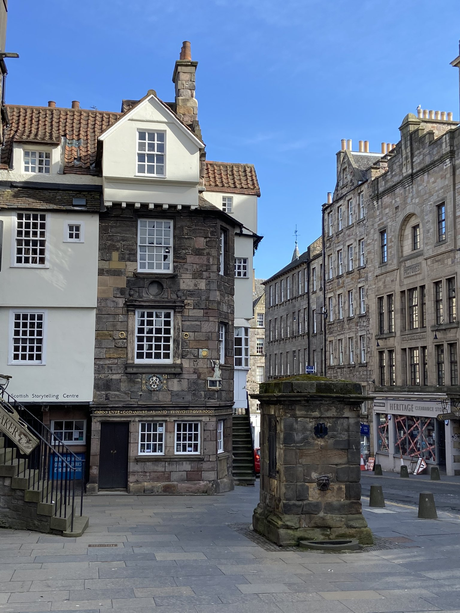 View of John Knox House from the Royal Mile on a sunny day, including the old water fountain on the pavement in front of it.
