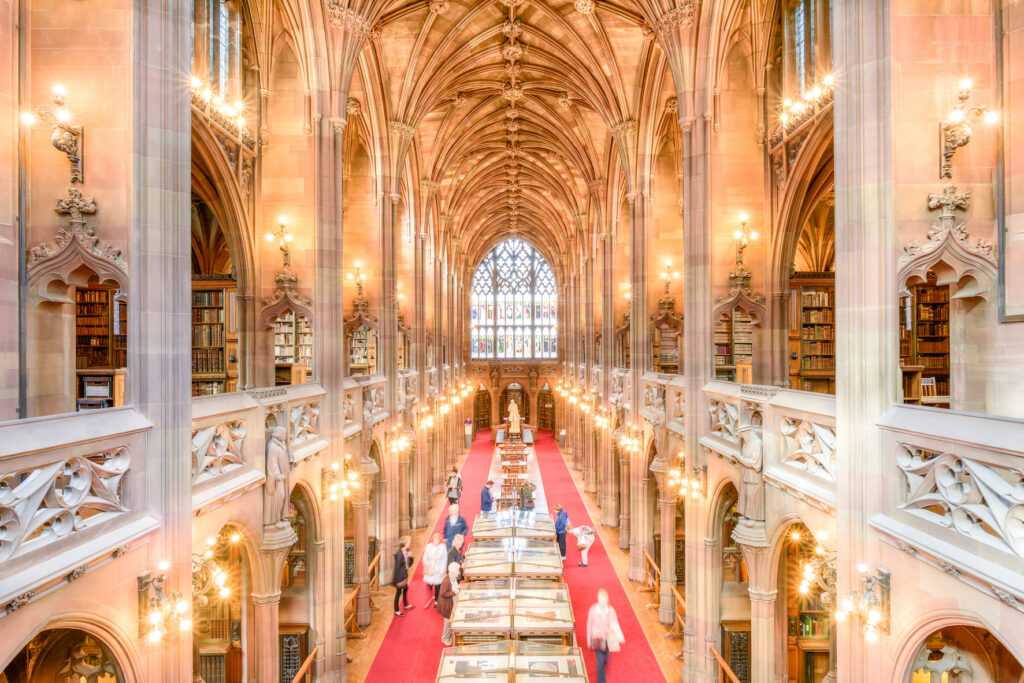 View of interior of Manchester library, with arches over mezzanine and ground floor.