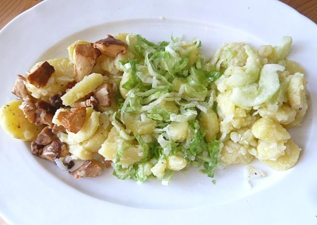 Restefrühstück mit verschiedenen Kartoffelsalaten, Würstchen und Käsespiegeleiern