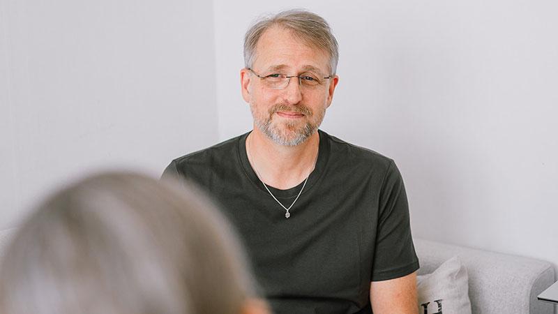 Din Psykolog Rickard Salomon har samtal med en person och ser ut att lyssna. Rickard erbjuder samtalsterapi till privatpersoner och företag.