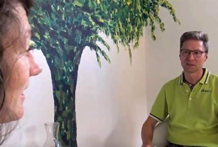 behandlersamtale i klinik med træ i baggrunden