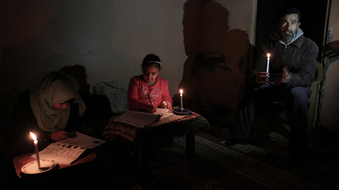 Palestinian girls study by candlelight in the Rafah refugee camp in the southern Gaza Strip, February 15, 2018 – the Gaza power Generating Company in Gaza Strip stopped working on 15 February 2018 because of a lack of fuel, officials said (photo: Abed Rahim Khatib)