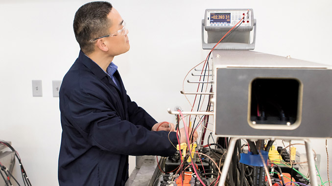 Enqin Gao, Chief Engineer of R&D, observes the voltages of battery cells during the PSoC Cycling test in Hammond Group's state-of-the-art lead battery lab