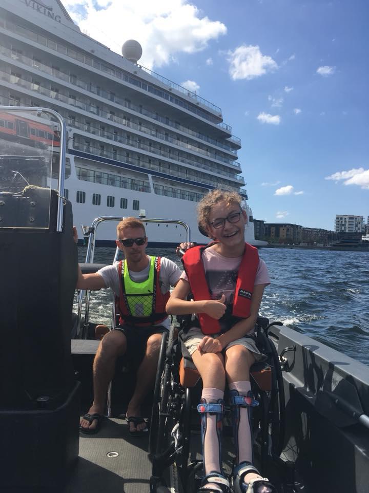 kørestols bruger i båd, med pædagog i baggrunden