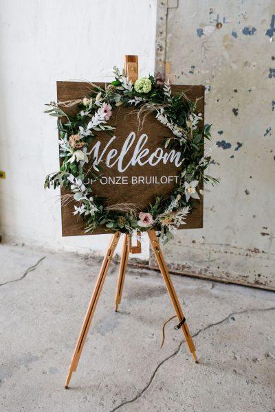 houten welkomsbord welkom op onze bruiloft met bloemen rustic wedding