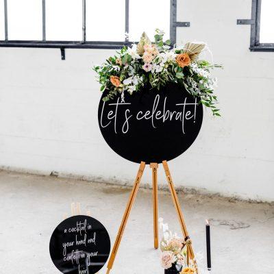 welkomsbord lets celebrate plexiglas zwart schildersezel huren bruiloft rond bord witte letters kalligrafie