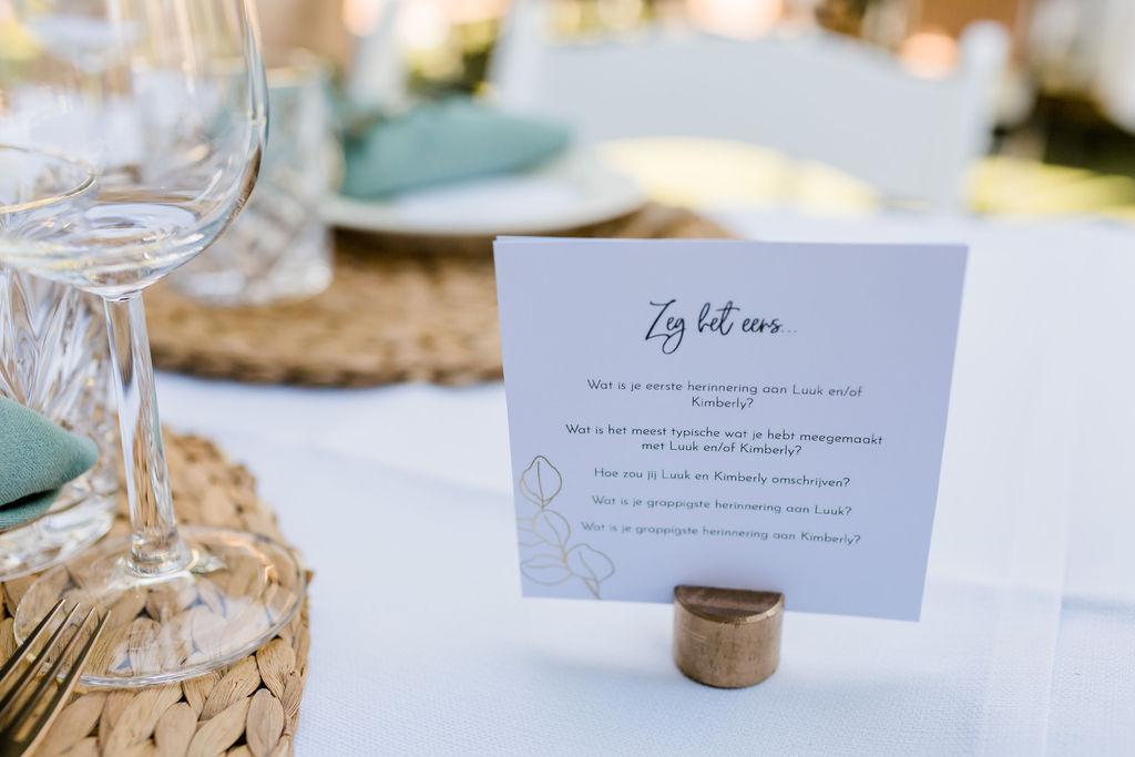 tafeldecoratie bruiloft trouwen buiten eten diner lange tafels menukaartjes kurk