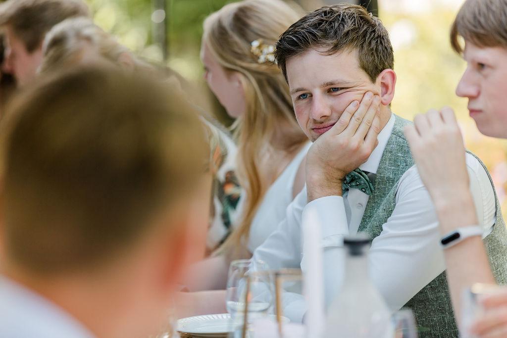 tafeldecoratie bruiloft trouwen buiten eten diner lange tafels bruidegom groen pak