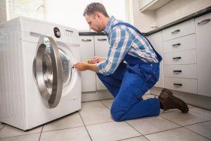 depositphotos_60927609-stock-photo-handyman-fixing-a-washing-machine
