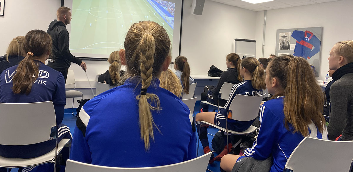 Bilde som viser jentespillere fra Hasle-Løren og andre samarbeidsklubber med Vålerenga på en videoanalyse før trening.