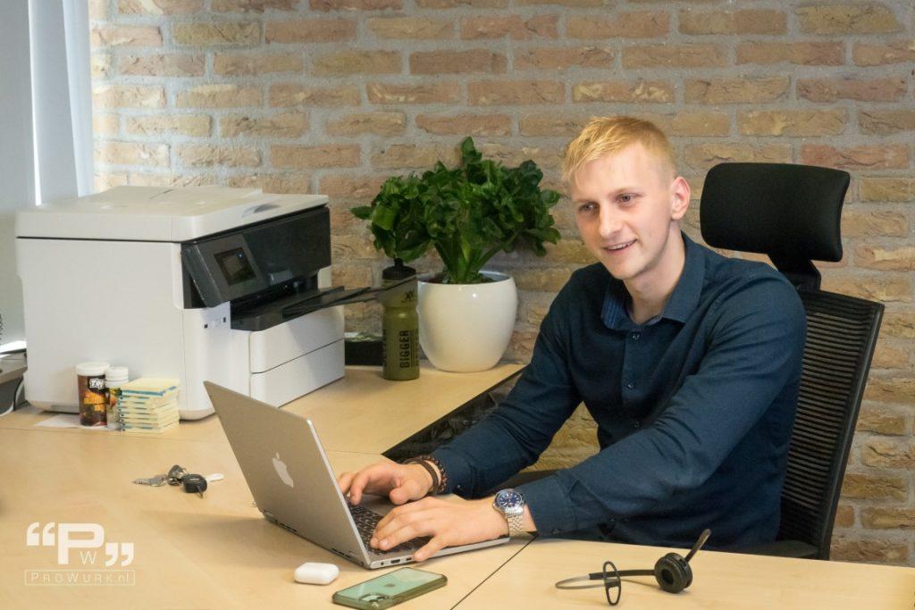 Man achter bruin bureau met telefoon laptop plant en printer. Illustratie voor artikel met tips voor afbeeldingen.