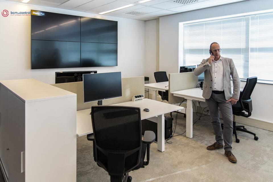 Bedrijfsfoto Man met telefoon in een leeg kantoor