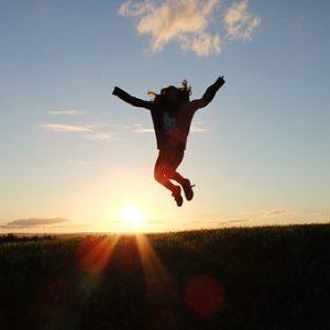 Person som hoppar mot bakgrund av solnedgång.