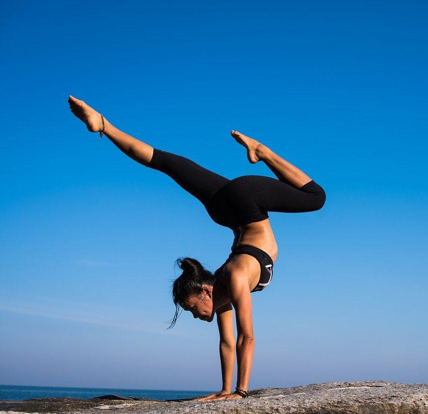 En idrottare balanserar på en klippa och visar prov på det slags fokus och driv som också du kan utveckla med hjälp av coachning och mental träning för idrottare med Susanne Sabith som din framstegscoach.