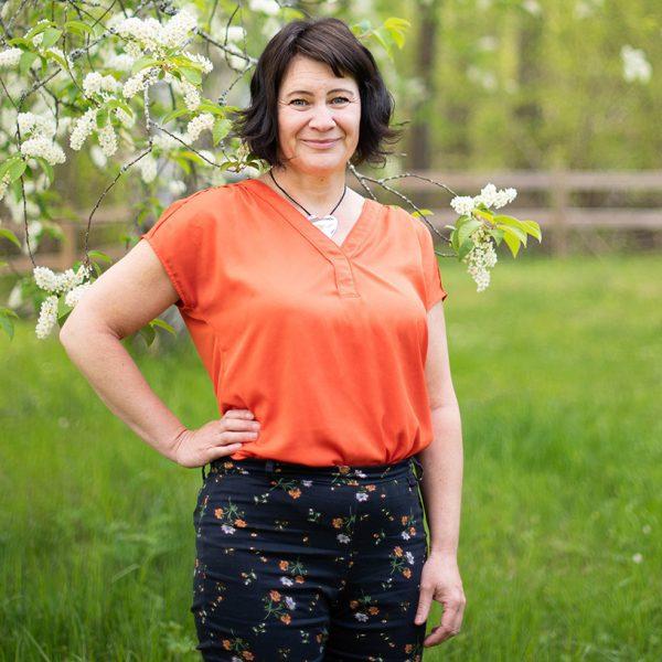Susanne Sabith - din framstegscoach - står framför en häggbuske och utstrålar glädje och energi. Välkommen att höra av dig till Susanne!